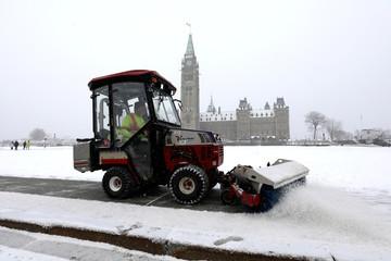 A worker clears a sidewalk as light snow falls on Parliament Hill in Ottawa