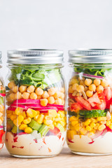 Jars with layering vegan salad for healthy lunch with place for text. The concept of fitness and vegetarian food.