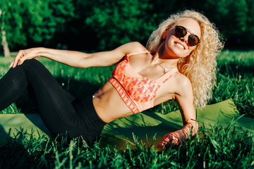 Photo of young curly woman in sunglasses lying on rug in park