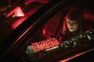 Young woman in car with smartphone and reflection of Kibiniai drive inscription