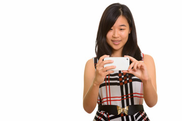 Young happy Asian businesswoman taking picture with mobile phone
