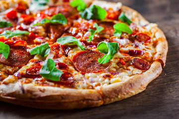 sliced Pepperoni Pizza with Mozzarella cheese, salami, chorizo, tomato sauce, pepper, Spices and Fresh arugula. Italian pizza on wooden table background