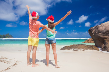 young couple in santa hats having fun on tropical beach. new year, Seychelles