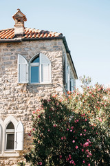 The facade of an ordinary old building with windows in Montenegro. Traditional housing. Near the garden with flowering trees.