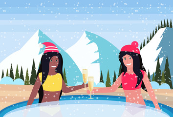 couple women hold champagne relax in outdoor swimming pool snowy mountains fir tree landscape background new year celebration concept flat horizontal