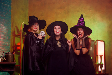 Portrait of three witches in black hats in dark room on background of mirror and rack