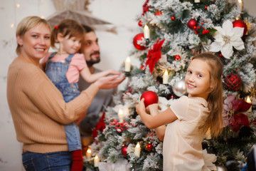 Photo of happy family near decorated New Year tree