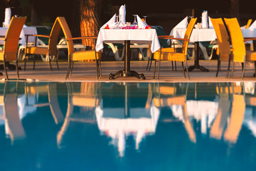 Chairs and table near pool at hotel restaurant