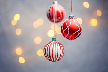 Image of three Christmas red balls with pattern on gray background with hot lights