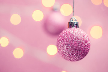 Picture of two Christmas pink balls on pink background with spots.