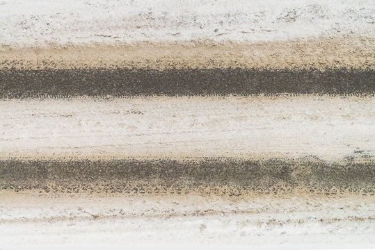 Snowy road close up. Car track in dirty snow. Track of tyres. View from above on highway. Textured winter realistic background with copy space. Abstract minimalist snowy weather texture.