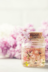 Glass jar with aroma oil and with lilac flowers for spa and aromatherapy. Spa concept.