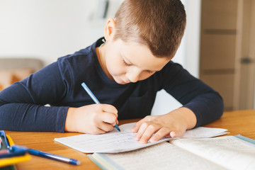 Schoolboy doing his homework on desk at home.