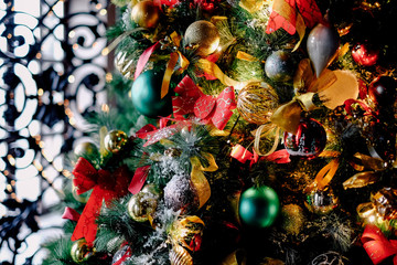 A lot of bright colorful toys on a decorated Christmas tree. Holiday close up with interior background with green, red, gold and other colors