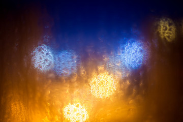 circles bokeh on wet glass in rainy weather at night.