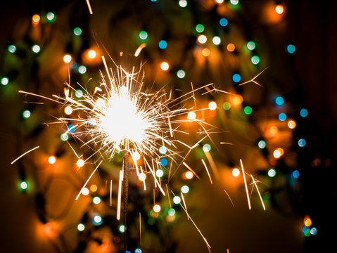 Glittering burning sparkler on colorful bokeh background.