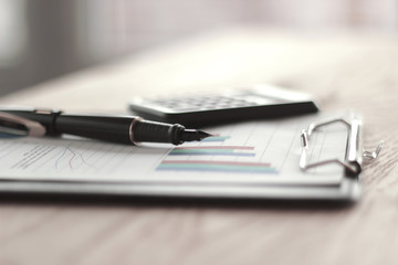 close up. pen, calculator and clipboard on wooden table. busines