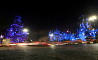 """Traffic moves in front of the Chhatrapati Shivaji Terminus railway station and Brihanmumbai Municipal Corporation, which were lit up in blue to support the global UNICEF """"Go Blue"""" campaign to mark Universal Children's Day in Mumbai"""