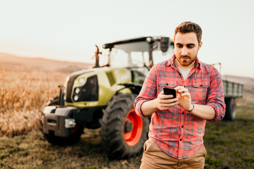 Farmer working and harvesting using smartphone in modern agriculture with tractor background Wall mural