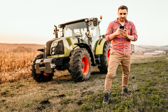 Farmer working and harvesting using smartphone in modern agriculture - tractor background
