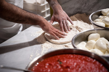 Preparing Pizza dought on a marble countertops. Tomato sauce and mozzarella in the foregound.