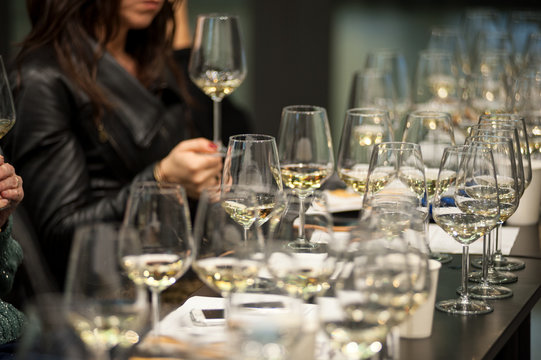 People tasting white wine and making notes at degustation card.
