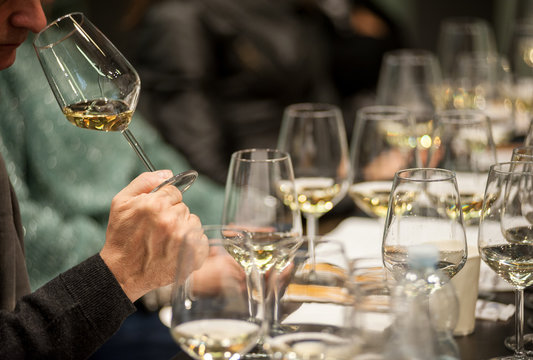 Man tasting white wine during a masterclass.