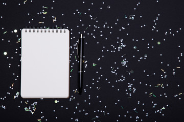 White notebook and pen on black background with holographic sparkles, stars and confetti.