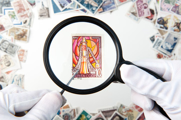 Hands holding postage stamp with a forceps and magnifier above the stamps on the table
