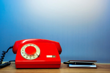 Outdated red rotary dial telephone