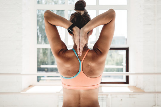 Back view on tanned fit woman stretching hands behind your back in sunny sport gym. Healthy girl wearing sportswear doing fitness exercises