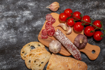 Salami sausage with tomatoes and garlic on a cutting board. Top view on dark background