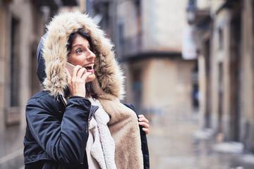 Mujer joven hablando por teléfono en un día de invierno lluvioso