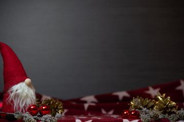 Weihnachtesdekoration auf einer weihnachtlichen Decke vor dunklem Hintergrund