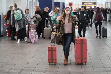 A woman carries her luggage in the Delta air terminal at LaGuardia Airport in New York