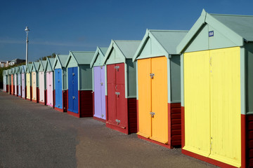 sixteen multicoloured beach huts in a row