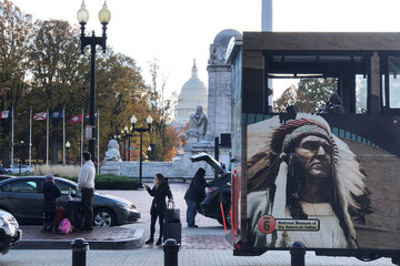 A tourist bus with a picture of a Native American pulls away from Union Station train and bus terminal as travelers stand in the drop-off lanes in Washington