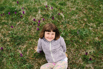 Young girl smiling while sitting on the grass