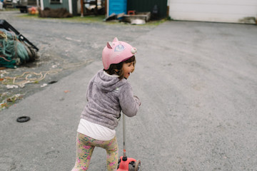 Young girl riding a scooter