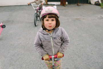 Girl sticking her tongue out while riding a scooter