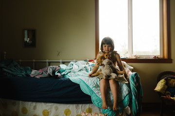 Young girl sitting on her bed with her toys on her lap
