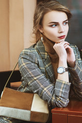 Young beautiful lady wearing stylish checkered blazer, turtleneck, silvery analog wrist watch, with suede brown, beige bag