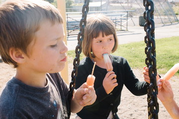 Three children eating popsicles at a park