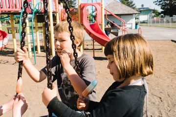Three children at a playground eating popsicles
