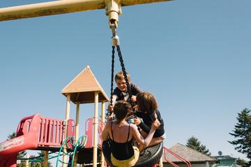 Three children having fun on a swing