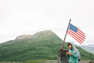Young girl standing near an American flag