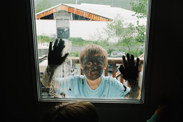 Boy with mud on his face and hands