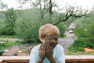 Boy puts mud on his face