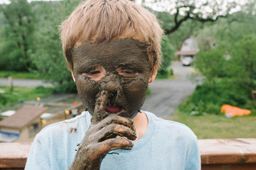 Young boy with mud on his face sticking his finger in his nose
