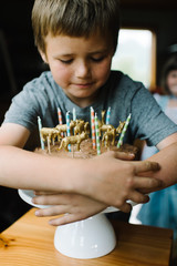 Boy wrapping his arms around a cake